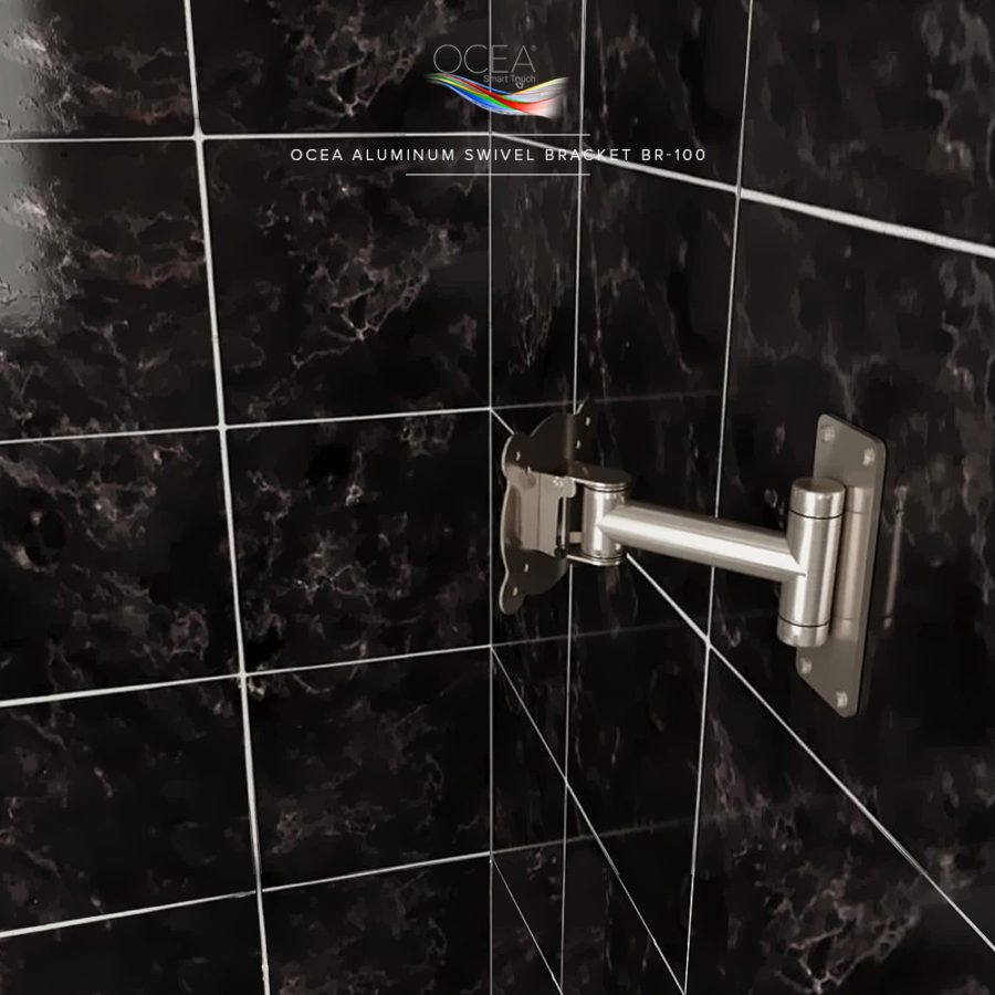 An aluminum swivel tv bracket attached to a bathroom wall in black marble tiles.